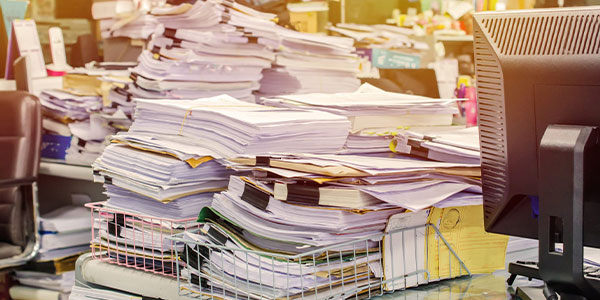 Legal documents that need review piling up on a legal practitioners desk.