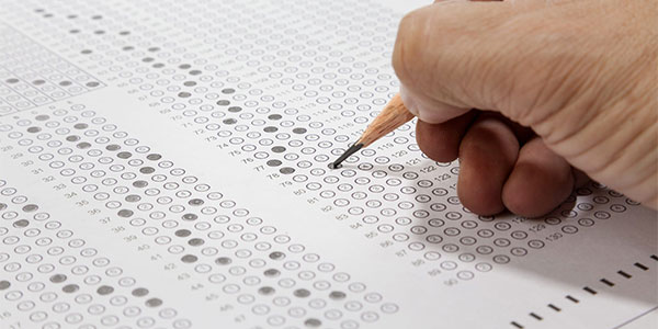 Hand holding a pencil and filling in classifiers on a scantron sheet.